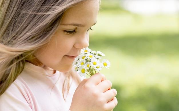 Gros plan, girl, sentir, bouquet, champ, fleurs
