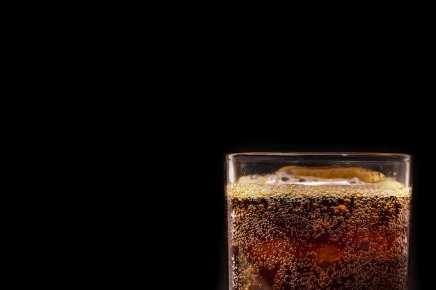 Gros plan, glace, cola, soda, boisson fraîche, à, bulle, sur, arrière-plan noir
