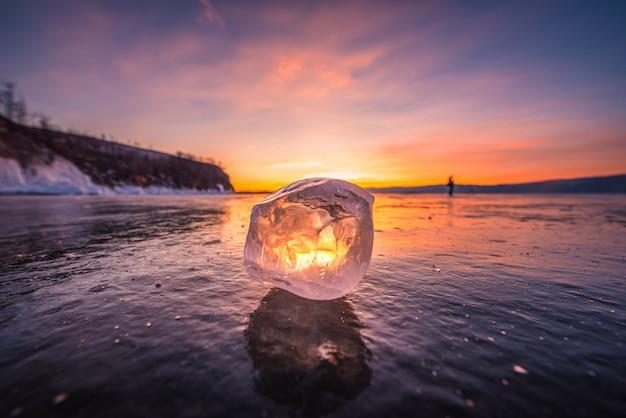 Gros plan de la glace naturelle brisant sur l'eau gelée au coucher du soleil dans le lac baïkal, en sibérie, en russie.