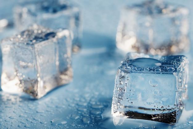 Gros plan de glaçons avec des gouttes d'eau de fonte éparpillées sur une table bleue. macro. glace rafraîchissante pour les boissons et cocktails lors d'une journée chaude et sensuelle.
