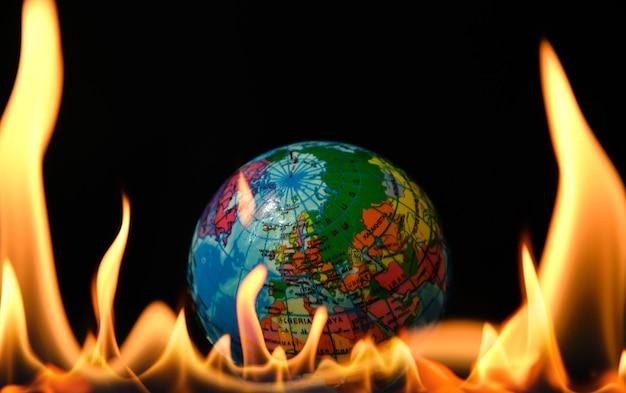 Gros plan sur le globe terrestre en flammes comme symbole du monde en feu, danger, crise politique, économique ou pandémie