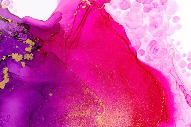 Gros plan sur des gouttes d'encre aquarelle dégradé rose et violet abstrait avec des stries dorées