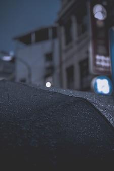 Gros plan des gouttes de pluie sur un parapluie