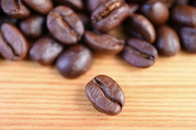 Gros plan d'un grain de café torréfié arabica avec une pile de grains de café floue en toile de fond