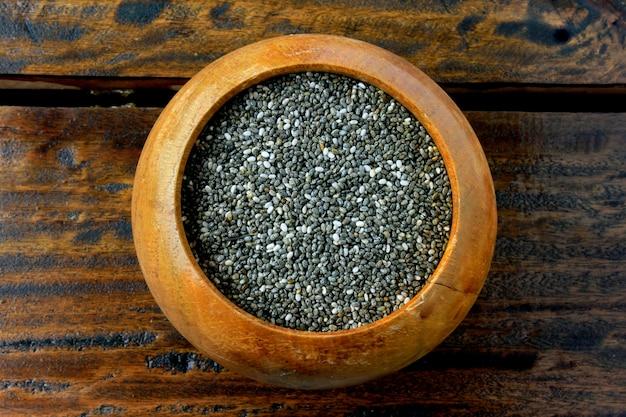 Gros plan de graines de chia dans un bol en bois isolé sur une table rustique