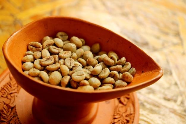 Gros plan des grains de café crus dans un bol en terre cuite de style thaï pour le café fait maison