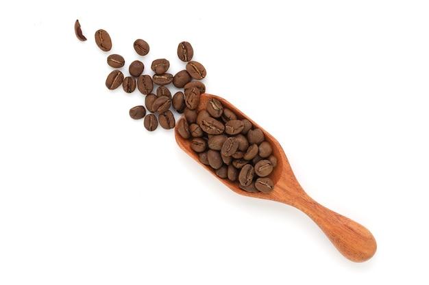 Gros plan et grains de café sur une cuillère en bois isolé sur une surface blanche