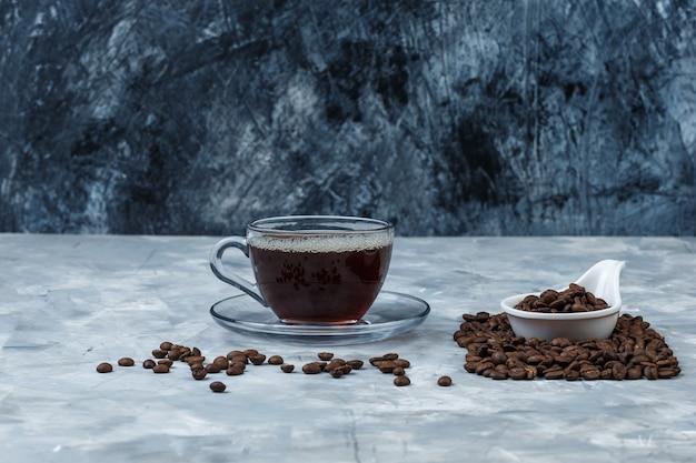 Gros plan de grains de café dans une cruche en porcelaine blanche avec une tasse de café sur fond de marbre bleu foncé et bleu clair. horizontal