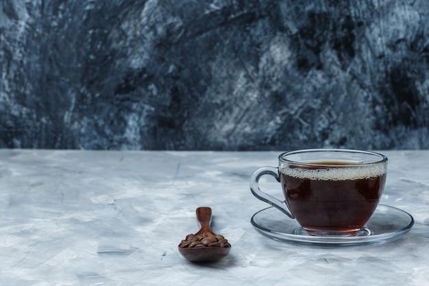 Gros plan de grains de café dans une cuillère en bois avec une tasse de café
