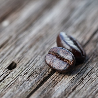 Gros plan de grains de café sur une table en bois grunge.