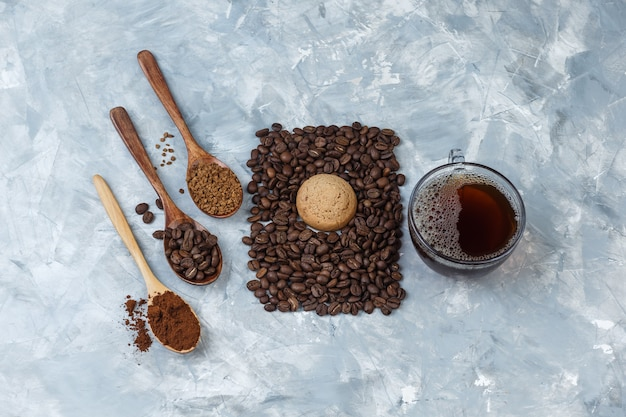 Gros plan de grains de café, tasse de café avec des grains de café, café instantané, farine de café dans des cuillères en bois, biscuit sur fond de marbre bleu clair. horizontal