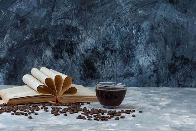 Gros plan de grains de café, tasse de café avec livre sur fond de marbre bleu clair et foncé. horizontal