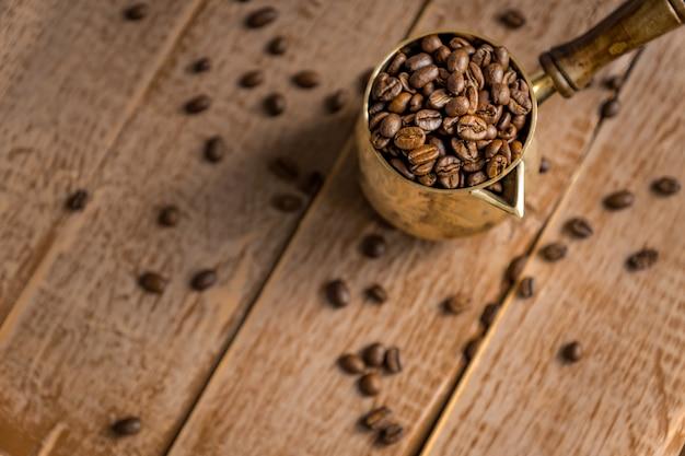 Gros plan de grains de café torréfiés frais en cezve (pot de café turc traditionnel) sur table en bois.