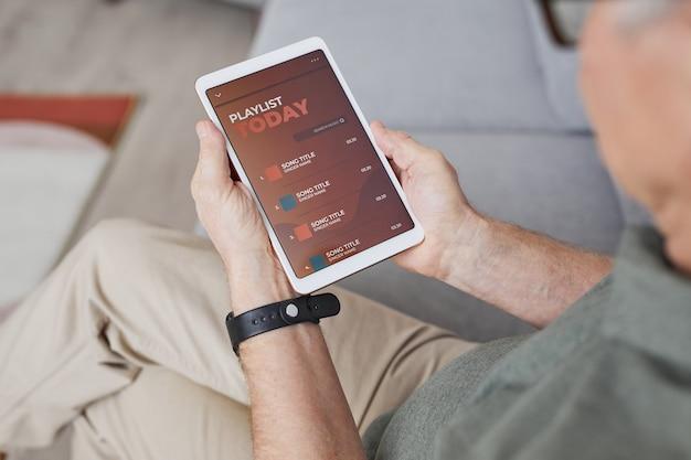 Gros plan en grand angle d'un homme senior moderne utilisant une tablette numérique avec une liste de lecture tout en écoutant de la musique à la maison, espace de copie