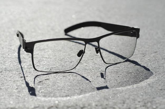 Gros plan grand angle de lunettes avec une ombre sur une surface grise