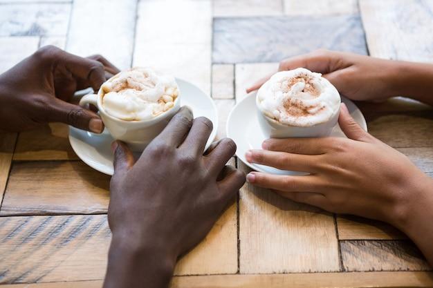 Gros plan grand angle de mains de couple multi ethnique tenant des tasses à café dans un café