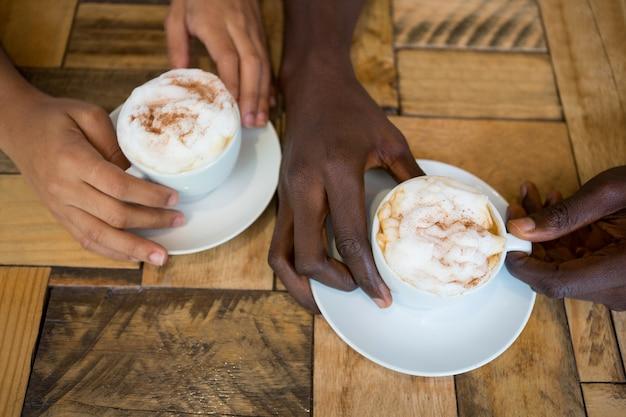 Gros plan grand angle de mains de couple tenant des tasses à café dans un café