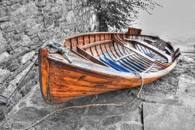 Gros plan grand angle tiré d'un bateau de pêche couché sur les pierres sur le corps du lac