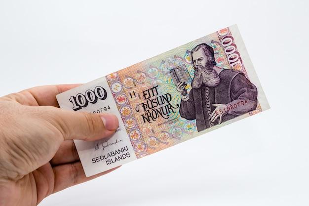 Gros plan grand angle tourné d'une personne tenant un billet sur un fond blanc