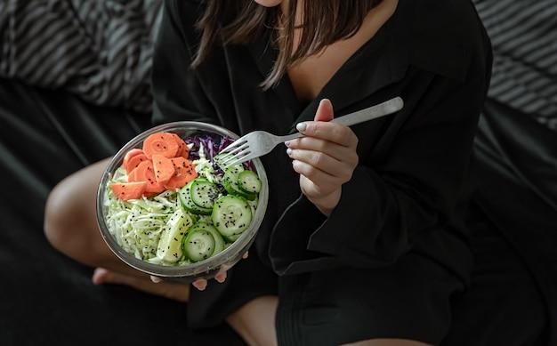 Gros plan d'un grand bol avec salade de légumes fraîchement préparés dans des mains féminines.