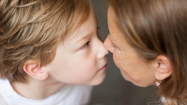 Gros plan grand-mère et enfant touchant le nez
