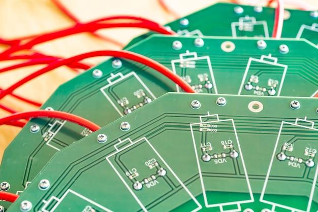 Gros plan sur un grand microcircuit vert avec des fils rouges à haute tension et des relais bleus qui y sont connectés dans une usine d'équipement militaire. le concept de nouvelles technologies haute tension en production