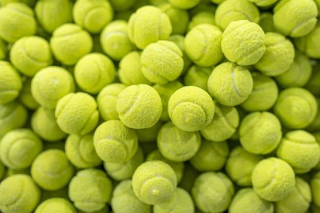 Gros plan d'un grand nombre de bonbons sucrés en forme de balles de tennis dans une pâtisserie