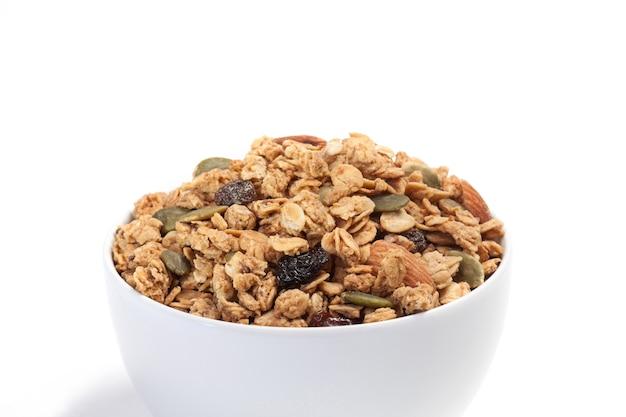 Gros plan granola sur bol blanc isolé sur fond blanc.