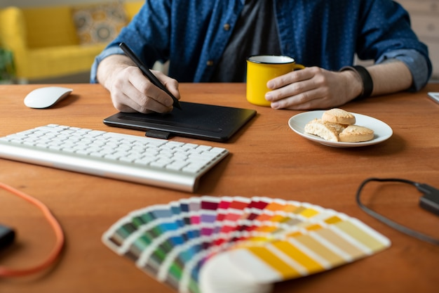 Gros plan d'un graphiste méconnaissable assis à table avec tasse et biscuits sur assiette et travaillant sur un produit visuel à l'aide de tablette numériseur