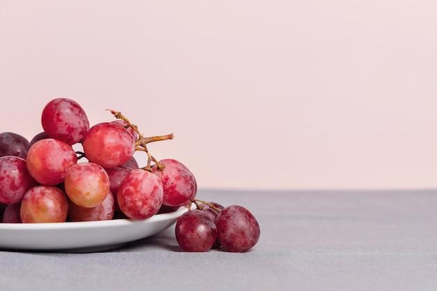 Gros plan d'une grappe de raisin sur fond rose