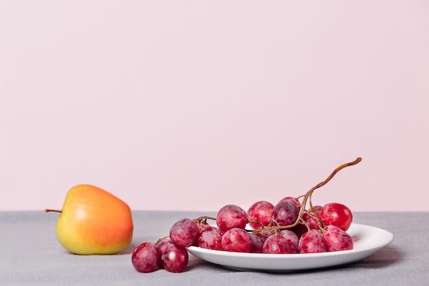 Gros plan d'une grappe de raisin et d'une pomme sur fond rose