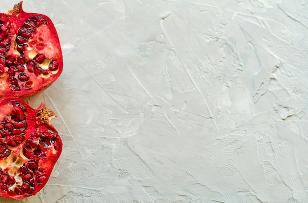 Gros plan de grenades mûres rouges - coupées et tranchées, mûres et savoureuses avec copie espace, fond de ciment gris