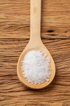 Gros plan de gros sel sur une cuillère en bois. toile de fond alimentaire.