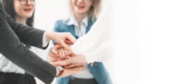 Gros plan.un groupe d'employés créant une tour de leurs mains. image floue pour le texte publicitaire. photo avec espace copie