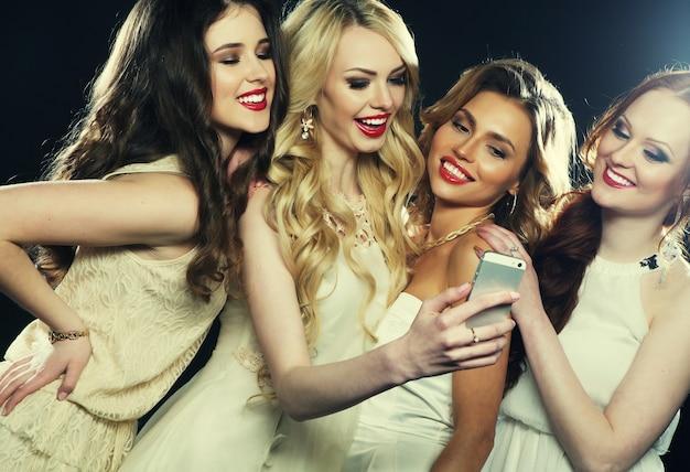 Gros plan sur un groupe de filles qui rient faisant la fête, prenez un selfie avec un smartphone