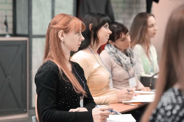 Gros plan.groupe de gens d'affaires avec presse-papiers assis à la réunion