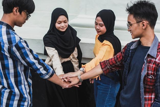 Gros plan groupe de jeunes gens faisant une poignée de main d'équipe