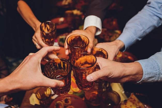 Gros plan d'un groupe de personnes tinter les verres avec du vin ou du champagne en face de bokeh