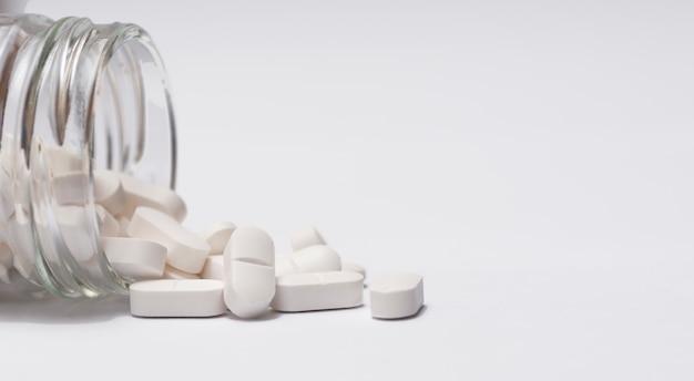 Gros plan d'un groupe de pilules blanches en bouteille de cristal.
