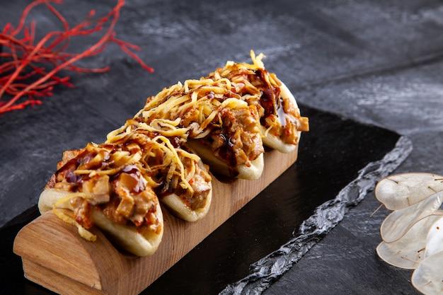 Gros plan sur gua bao, petits pains cuits à la vapeur avec de la viande. bao servi avec une garniture savoureuse sur le noir. cuisine asiatique. sandwich asiatique cuit à la vapeur gua bao. restauration rapide de style japonais. mise au point sélective