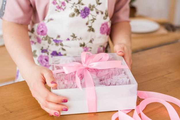 Gros plan des guimauves maison. mains de femme avec une boîte cadeau guimauve