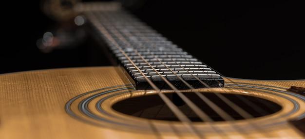 Gros plan sur une guitare et des cordes avec une faible profondeur de champ, un flou artistique.