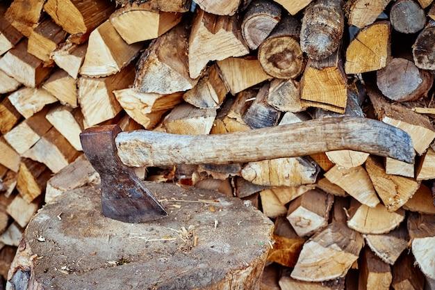 Gros plan d'une hache contre fond de bois de chauffage