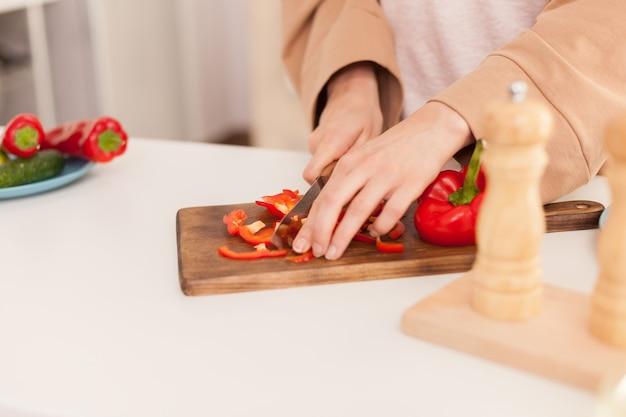 Gros plan de hacher le poivron sur une planche à découper dans la cuisine.
