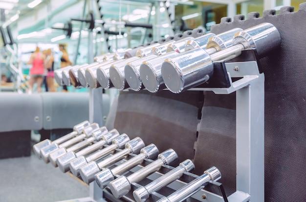 Gros plan d'haltères métalliques prêts à l'emploi dans un centre de remise en forme avec des sportifs défocalisés. concept d'équipement de musculation.