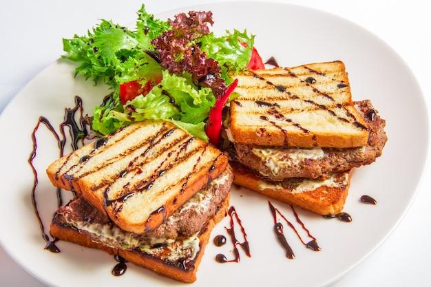 Gros plan hamburger avec bacon et sauce au fromage, salade, vinaigrette aux olives