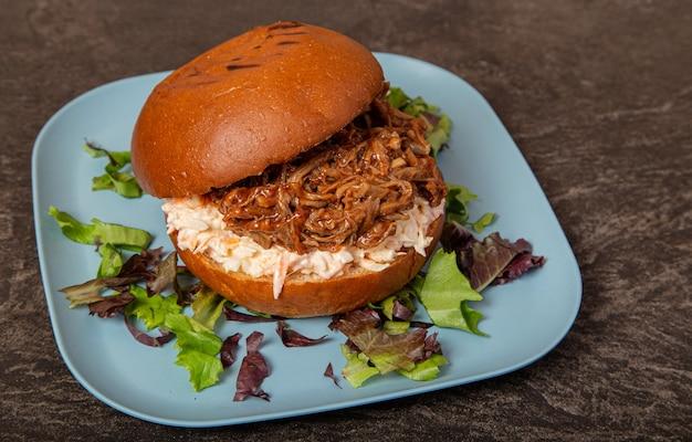 Gros plan d'un hamburger de viande tiré juteux et ouvert entouré de légumes verts sur une plaque bleue