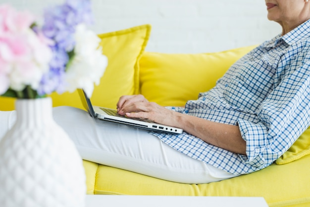 Gros plan de haute femme assise sur un canapé en tapant sur un ordinateur portable