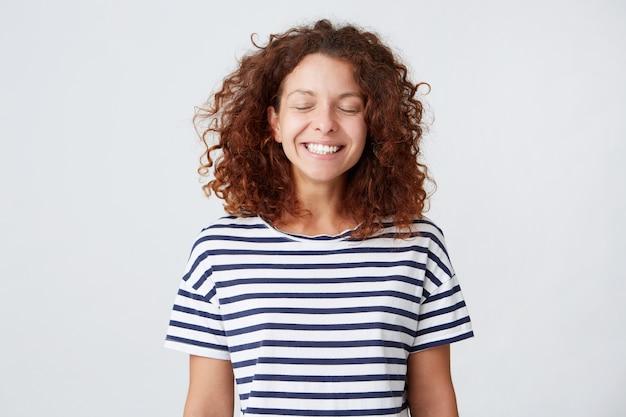 Gros plan de l'heureuse belle jeune femme aux cheveux bouclés porte un t-shirt rayé