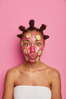 Gros plan sur l'heureuse femme ethnique aime appliquer un masque facial isolé